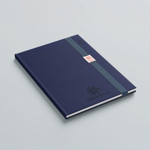 Κατασκευή και τοποθέτηση μεταλλικής πλακέτας, με χάραξη λογοτύπου σε χρώμα επιλογής, προσαρμοσμένη στο λάστιχο του βιβλίου, σχεδιασμένη εξειδικευμένα για τον κάθε πελάτη.