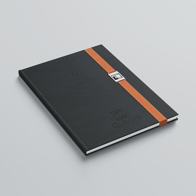 Κατασκευή και τοποθέτηση μεταλλικής πλακέτας, με χάραξη λογοτύπου σε χρώμα επιλογής προσαρμοσμένη στο λάστιχο του βιβλίου, σχεδιασμένη εξειδικευμένα για τον κάθε πελάτη